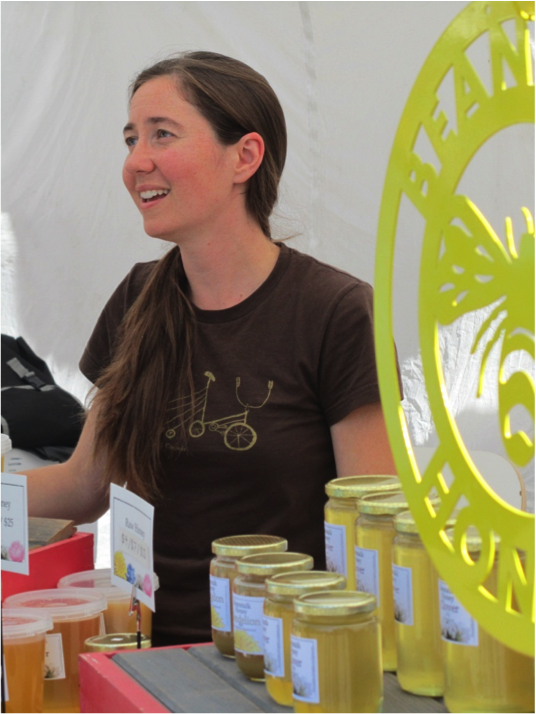 Tracey at her farmers market stall with honey in the foreground