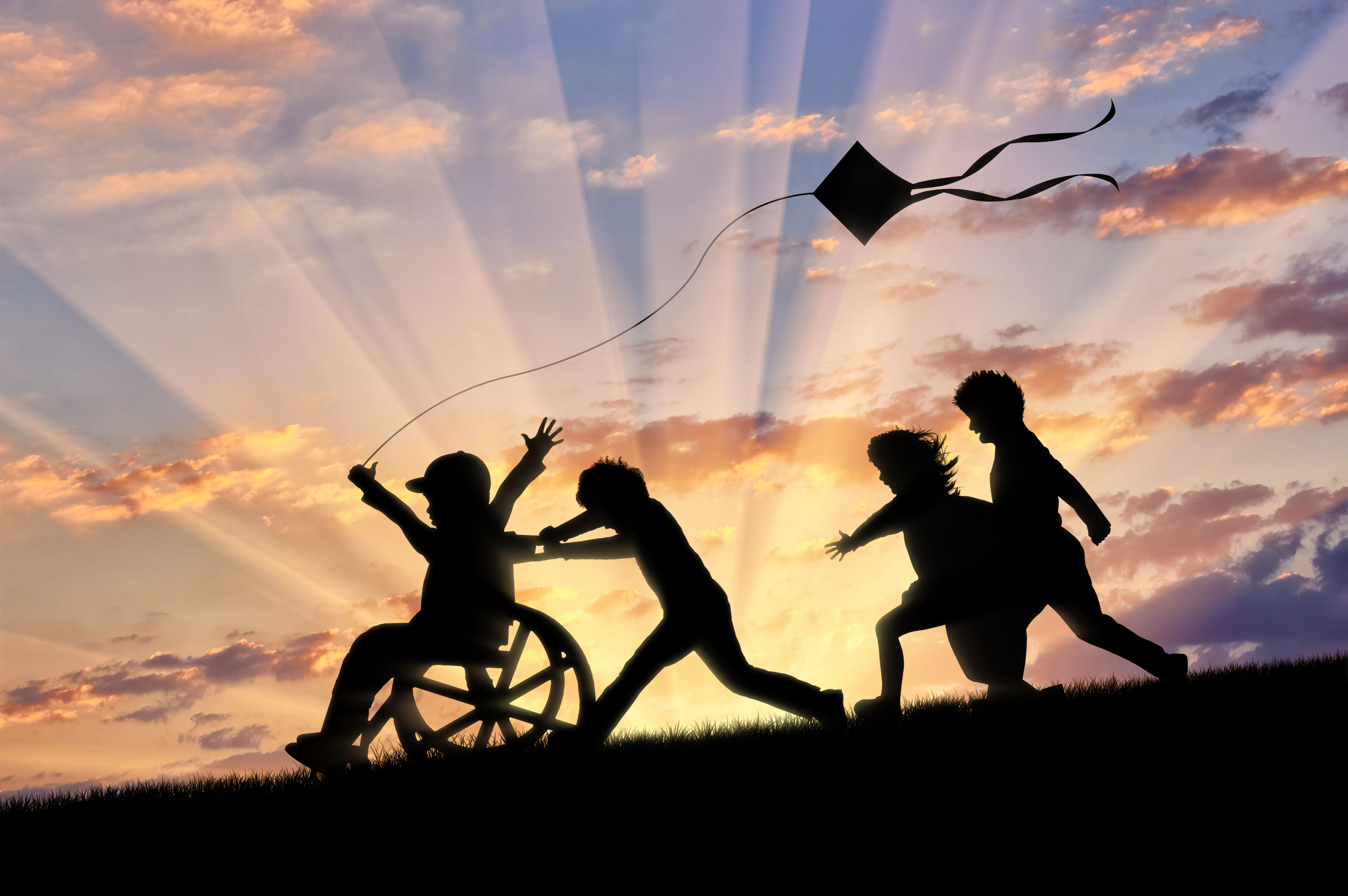 An image of a child in a wheelchair, holding a kite. Being pushed by other children playing too. Image is for decorative purposes only.